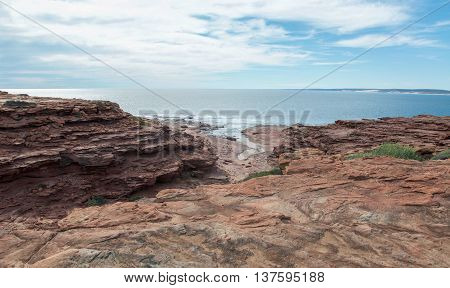 Indian Ocean seascape from the sandstone bluffs and rocky edges at Red Bluff beach under a blue sky with clouds in Kalbarri, Western Australia.