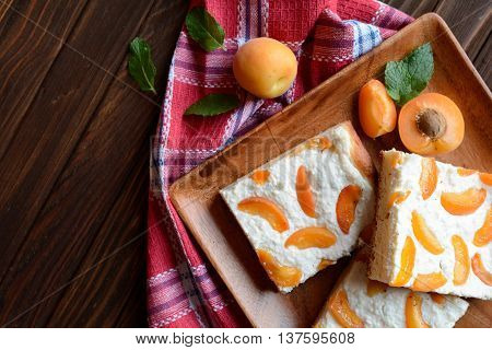 Apricot pie with curd on wooden background