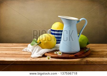 Still life ith lemons and blue enamel jug on wooden table