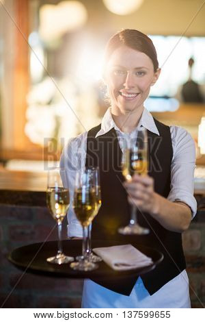 Portrait of waitress offering a glass of champagne in restaurant