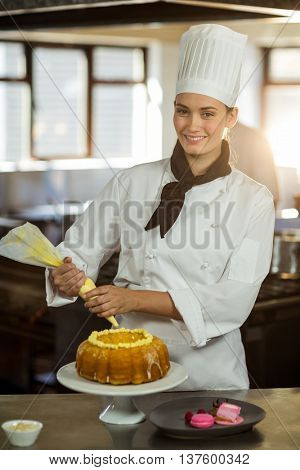 Portrait of female chef piping icing on cake in a commercial kitchen
