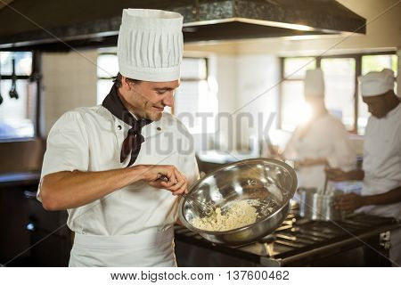 Smiling chef mixing dough in a commercial kitchen
