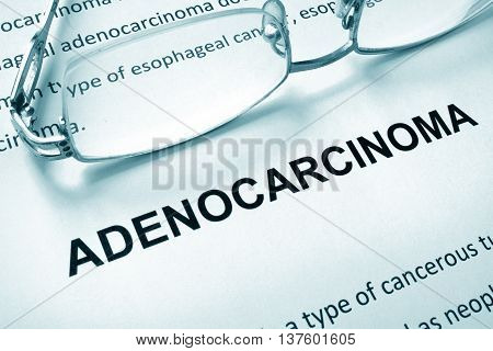 Paper with word adenocarcinoma and glasses. Medical concept.
