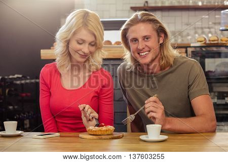 Couple eating a cake togheter in the cafe