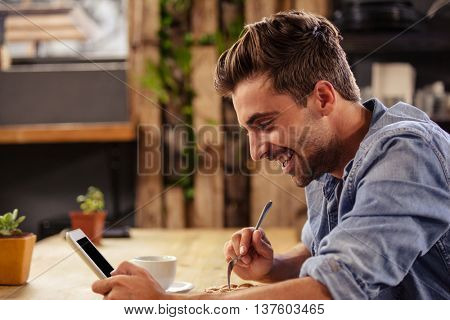 Profile view of hipster man using tablet at cafe while eating pastry