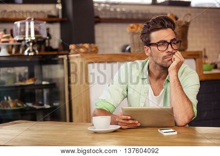 Bored hipster man using tablet computer at cafe