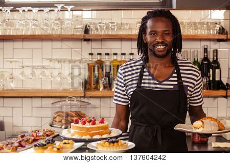 Handsome waiter standing at coffee shop