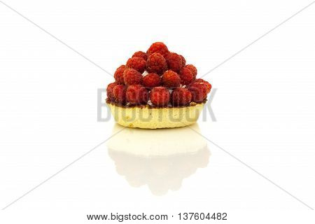 Tartlet pastry with cream and fresh raspberries with reflection on white background.