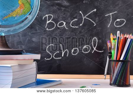 Back To School Written On Blackboard In Center With Tools