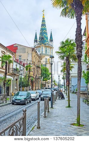 BATUMI GEORGIA - MAY 24 2016: The narrow street with palms leads to the Europe Square and ends with the slender astronomical tower of the former National Bank building on May 24 in Batumi.