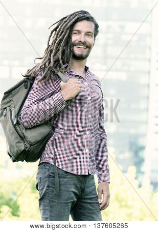 Handsome young man with dreadlocks walking in city with backpack on one shoulder