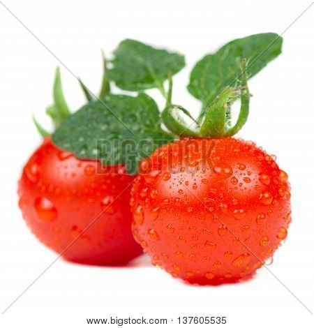 Two red cherry tomatoes with water drops isolated on a white background