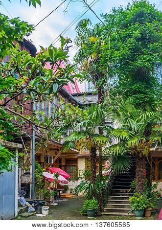 BATUMI GEORGIA - MAY 24 2016: The city is full of the tiny yards with shady trees plants in pots sunshades and other details making it cozy and quiet places on May 24 in Batumi.