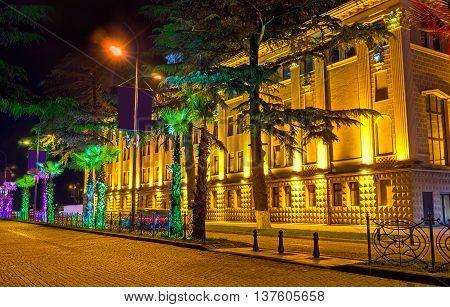 The colorful palms decorate the evening city street along the Drama Theater Batumi Georgia.