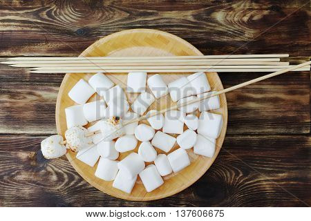 Fluffy white marshmallow in wooden bowl on old wooden table with long skewers
