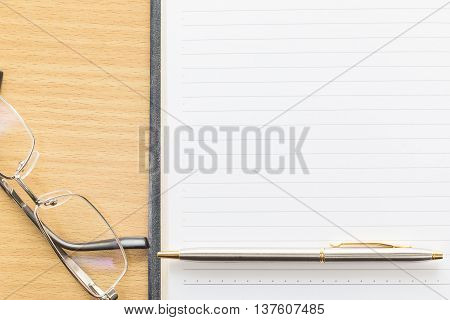 Eyeglasses And Pen On Notepad With Blank Page