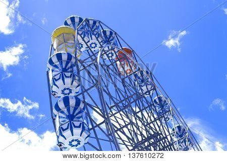 Giant ferris wheel against blue sky and white cloud