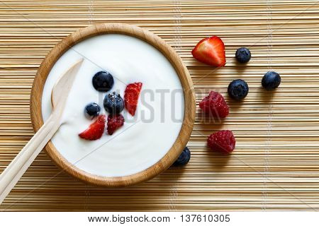 Wooden Bowl Of White Yoghurt With Wooden Spoon Inside On Bamboo Matt From Above. Next To Berries.