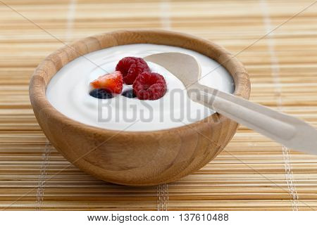 Wooden Bowl Of White Yoghurt With Wooden Spoon Inside On Bamboo Matt. Garnished With Fruit.