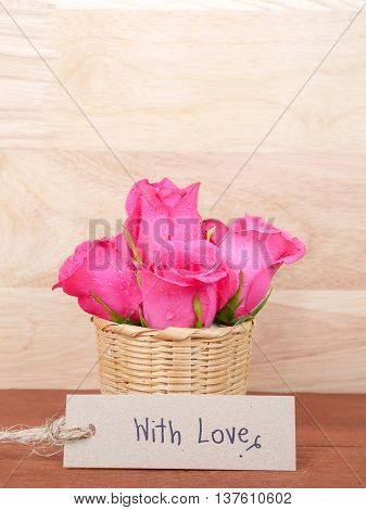 Pink rose flower in the basket and handwriting With love on brown label paper with wood background - Vertical