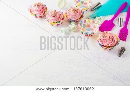 Pink cupcakes and cookware invitation background. Birthday cupcakes. Birthday background. Homemade cupcake. Birthday mockup.