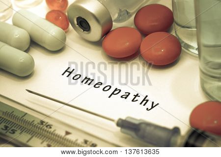 Homeopathy - diagnosis written on a white piece of paper. Syringe and vaccine with drugs