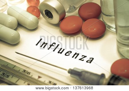Influenza - diagnosis written on a white piece of paper. Syringe and vaccine with drugs.
