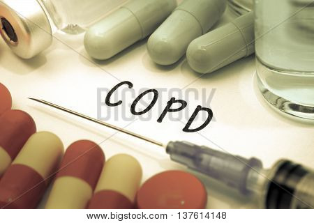 COPD - diagnosis written on a white piece of paper. Syringe and vaccine with drugs.