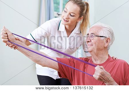 Senior Male Working With Physiotherapist And Resistance Band