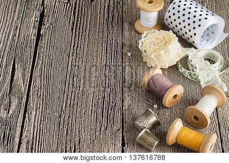 Sewing supplies. Spools of thread, colored ribbons, thimbles and needles on a wooden table.