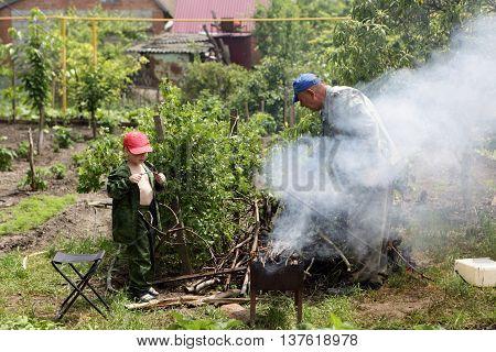 Grandfather and his grandson preparing barbecue at backyard
