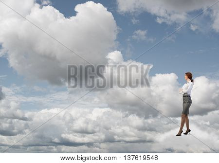Smiling confident businesswoman in sky standing on cloud