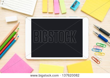 Desk above table top view of stationery items - pen pencil colored pencils paper clips sticky notes sharpener eraser notepad notebook and tablet on wooden background