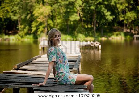 Blondie smiling girl in nature at sunset