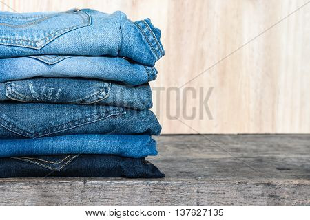 Jeans stacked on a wooden table unisex trendy fashion