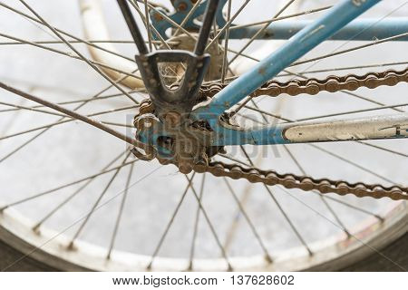old behind wheel of bycicle and rusty chain for movement