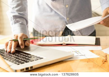 Bussiness businessman working use laptop in office for discussing documents and ideas with soft focus vintage tone