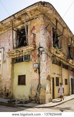 HAVANA - CUBA JUNE 19, 2016: Man walks by one of the many crumbling buildings at the corner of Calle Inquisidor in the La Habana Vieja neighborhood