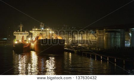 The tanker at a pier on a tank farm at night