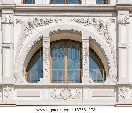 White window in the shape of a semicircle crossed by decorated columns.