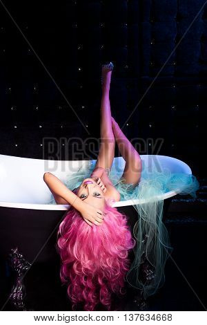 Beautiful, pretty, happy rose, long and curly hair, barbie, lies in bathroom, bath Black background