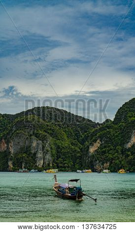 Traditional Thai Longtail boats and new speed boats on phi phi island , thailand ,