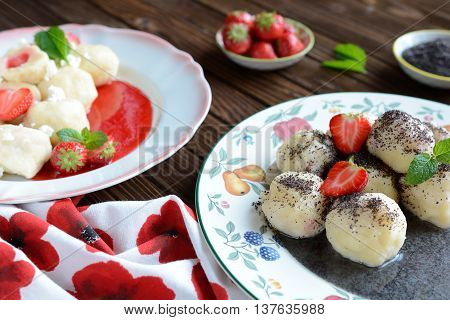 Two plates of sweet boiled dumplings filled with strawberries with a curd and poppy seed