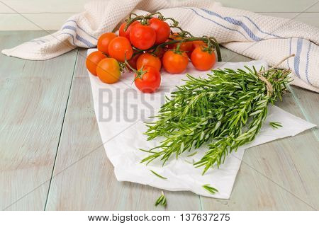 Fresh tomatoes and rosemary on wooden surface