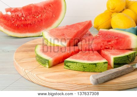 Slices of watermelon on a wood cutting board and wooden background