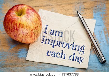 I am improving each day - self development concept or positive affirmation - handwriting on a napkin with an apple