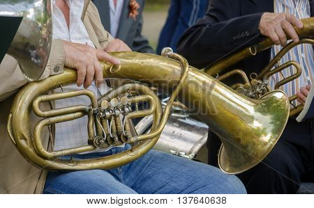 Hands of older musicians and old musical instruments outdoor