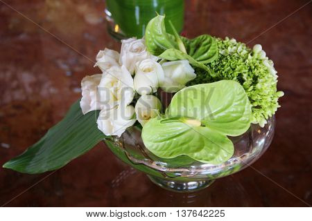 White roses and tropical leafs in a vase