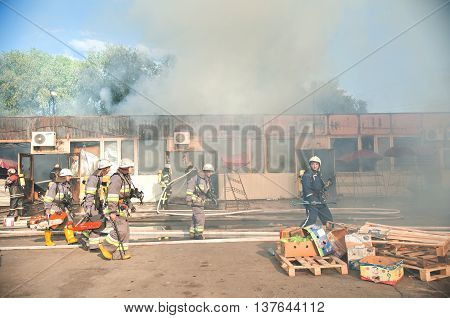 Kiev Ukraine - June 2016: Firefighters extinguish a large fire at Troyeschina market with water and fire extinguishers on June 3 2016 in Kiev