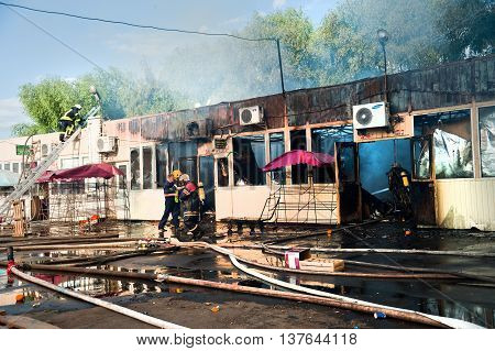 Kiev Ukraine - June 2016: Firefighters extinguish a large fire at Troyeschina market with water and fire extinguishers.